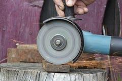 Un homme travaillant avec l'outil électrique de broyeur sur la structure métallique dans l'usine, voler d'étincelles images stock