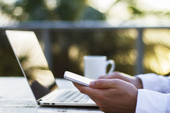 Un homme travaillant avec un ordinateur portable et un téléphone portable au lever de soleil Image stock