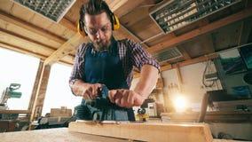 Un homme travaille avec du bois, utilisant un outil de menuiserie clips vidéos