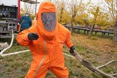 Un homme travaille dans un costume chimique orange de protection image libre de droits