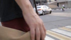 Un homme traverse la route à un passage pour piétons, dans les mains d'une caméra sur son sac d'épaule sur le fond d'a banque de vidéos
