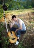 Un homme triste avec une guitare contre le bris Image libre de droits