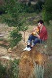 Un homme triste avec une guitare contre le bris 2 Images libres de droits