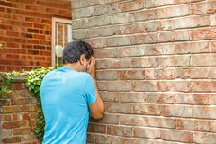 Un homme triste pleure se penchant sur un mur de briques d'une maison photo stock