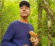 Un homme a trouvé un champignon dans la forêt et est fier image libre de droits