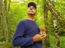 Un homme a trouvé un champignon dans la forêt et est fier photographie stock libre de droits