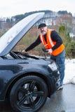 Un homme a une panne de voiture sur une route de campagne images libres de droits