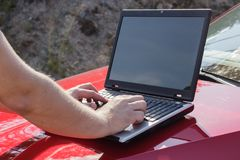 Un homme utilise un ordinateur portable sur le capot d'une voiture photo stock