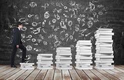 Un homme va consommation les escaliers qui sont faits de livres blancs Des icônes éducatives sont dessinées sur le tableau noir Photo libre de droits