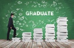 Un homme va consommation les escaliers qui sont faits de livres blancs Le diplômé de mot est sur le tableau vert Images stock