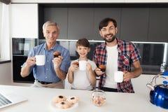 Un homme, un vieil homme et un garçon posent dans la cuisine avec des tasses de thé et de petits pains Ils sourient Photo libre de droits