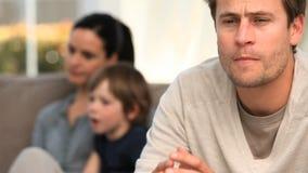 Un homme worring tandis que sa famille est sur le sofa banque de vidéos