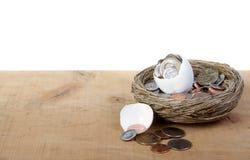 Un huevo abierto agrietado con las monedas que se derraman hacia fuera Imágenes de archivo libres de regalías