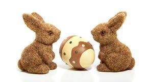 Un huevo de Pascua entre dos conejitos fotografía de archivo libre de regalías