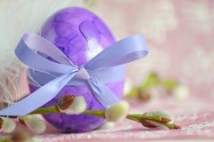 Un huevo de Pascua púrpura con las ramas del sauce imagen de archivo