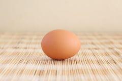 Un huevo en una estera de lugar marrón de la paja fotos de archivo libres de regalías