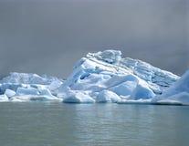 Un iceberg lumineux avec les nuages foncés Photos stock