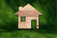 un'icona della casa da struttura di legno sul fondo dell'erba Fotografia Stock Libera da Diritti