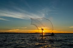 Un-identified silhouette fisher man on boat fishing by throwing. Fishing net to river during sunset in rural of Thailand stock images