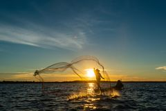Un-identified silhouette fisher man on boat fishing by throwing. Fishing net to river during sunset in rural of Thailand stock photos