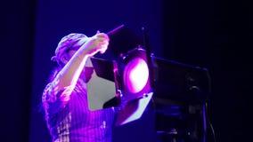 Un iluminador de la mujer joven pone una cortina del proyector del perfil y los abre almacen de video