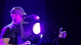 Un iluminador del hombre pone la cortina del proyector del perfil y los abre metrajes