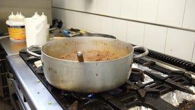 Un imbécile de casserole de sauce à viande sur les cuiseurs avec le gaz dessus, 4K banque de vidéos