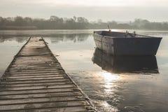 Un'imbarcazione a remi galleggia alla deriva su un lago congelato accanto ad un passaggio pedonale vuoto immagine stock libera da diritti