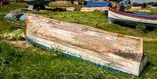 Un'imbarcazione a remi rovesciata in un campo con altre barche fotografia stock libera da diritti