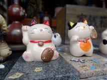 Un'immagine alta vicina di due figure di Maneki-Neko fotografie stock libere da diritti