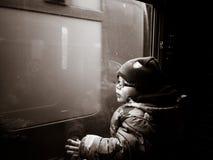 Giovane ragazzo che guarda da una finestra del treno immagini stock