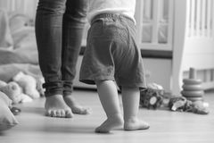 Un'immagine in bianco e nero di 10 mesi del neonato che cammina alla sua m. Fotografia Stock Libera da Diritti