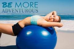 Un'immagine composita della donna di misura che si trova sulla palla di esercizio all'allungamento della spiaggia Fotografia Stock