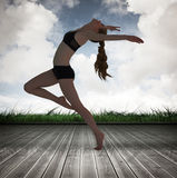 Un'immagine composita della vista laterale di un allungamento sportivo della giovane donna Fotografie Stock