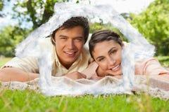 Un'immagine composita di due amici che si trovano insieme su una coperta mentre sorridendo Fotografia Stock
