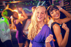 Un'immagine composita di due belle donne che ballano sulla pista da ballo Fotografie Stock Libere da Diritti