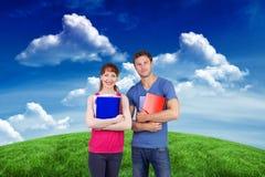 Un'immagine composita di due studenti entrambe con i blocchi note Immagine Stock