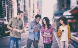 Un'immagine composita di quattro amici alla moda che esaminano compressa e che tengono i telefoni immagini stock libere da diritti