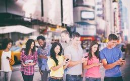 Un'immagine composita di quattro amici che stanno al lato leggermente che invia manda un sms a immagini stock