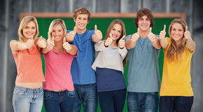 Un'immagine composita di sei amici che danno i pollici su come sorridono Immagine Stock