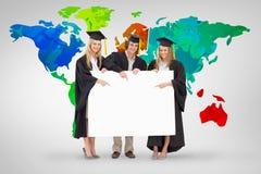 Un'immagine composita di tre studenti in abito laureato che tiene e che indica un segno in bianco Fotografie Stock Libere da Diritti