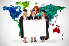 Un'immagine composita di tre studenti in abito laureato che tiene un segno in bianco Immagini Stock Libere da Diritti
