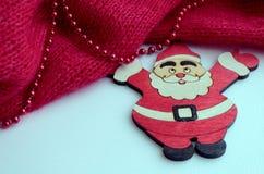 un'immagine con una tela tricottata rossa su cui le perle si trovano Vicino è una figura di Santa Claus fotografia stock