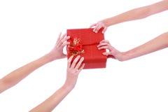 Un'immagine del primo piano delle due mani della donna con il contenitore di regalo rosso Fotografia Stock Libera da Diritti