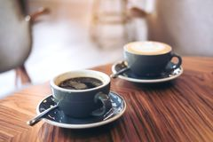 Un'immagine del primo piano di due tazze blu del caffè caldo del latte e del caffè di Americano sulla tavola di legno d'annata Immagine Stock Libera da Diritti