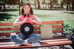 Un'immagine del sittin della ragazza sul banco con le sue gambe attraversate e che mostrano il segno di amore con le sue mani Il  Fotografie Stock