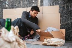 Un'immagine dell'uomo che si siede sul cartone sulla terra Vive fuori Il tipo sta raggiungendo la scatola e sta esaminandola Fotografia Stock