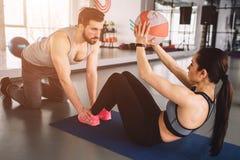 Un'immagine della ragazza che fa un pò di ABS si esercita con la palla mentre il suo partner di sport sta tenendo le sue gambe gi fotografia stock