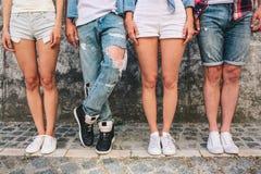Un'immagine delle gambe del ` di anni dell'adolescenza Tre di loro stanno stando diritti mentre l'uomo in jeans sta tenendo la ga Immagine Stock