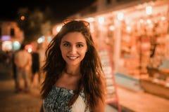 Un'immagine di colore di una donna che sorride sulla via alla notte fotografia stock libera da diritti